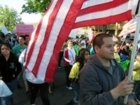 Julio Guzman, 20, carries a flag during a march for immigration reform on Wednesday, May 1, 2013 in Yakima, Wash. (AP Photo/Shannon Dininny)