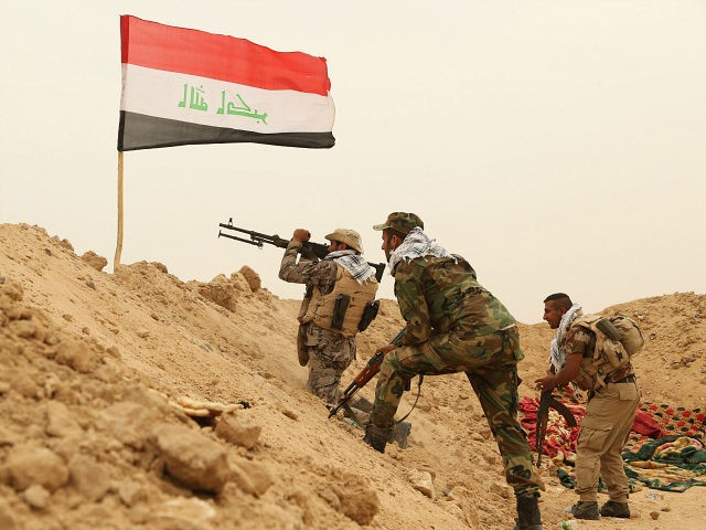 Fighters from the Badr Brigades Shiite militia clash with Islamic State militant group at the front line, on the outskirts of Fallujah, Anbar province, Iraq, Monday, June 1, 2015. Three Islamic State suicide bombers targeted a police base in the Tharthar area north of Ramadi, some 30 miles (48 kilometers) …