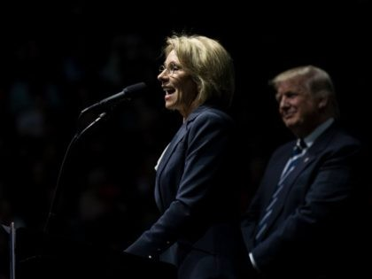 Betsy DeVos, his nominee for Secretary of Education, speaks as President-elect Donald Trump looks on at the DeltaPlex Arena, December 9, 2016 in Grand Rapids, Michigan. President-elect Donald Trump is continuing his victory tour across the country. (Photo by Drew Angerer/Getty Images)