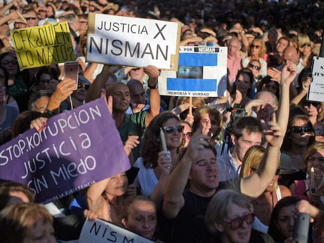 People hold signs during a vigil on the first anniversary of Argentinian prosecutor Alberto Nisman's mysterious death in Buenos Aires, on January 18, 2016. The prosecutor died in mysterious circumstances in January 18, 2015, after accusing Argentina's then president, Cristina Fernandez de Kirchner, of obstructing his investigation of a 1994 bombing at a Buenos Aires Jewish center. AFP PHOTO/EITAN ABRAMOVICH. / AFP / EITAN ABRAMOVICH (Photo credit should read EITAN ABRAMOVICH/AFP/Getty Images)