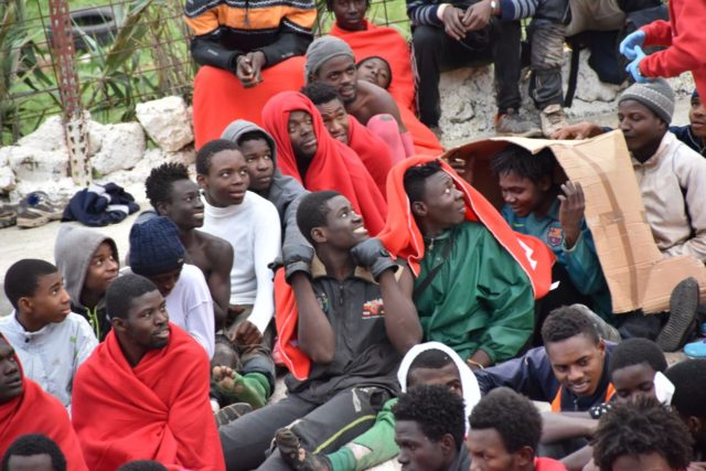 Migrants sit on the ground in El Tarajal, Ceuta, close to the boarder with Morocco on December 9, 2016 after being rounded up by police to be attended to by Red Cross personnel and taken to the Center for Temporary Stay of Immigrants (CETI) after nearly 400 migrants forced their