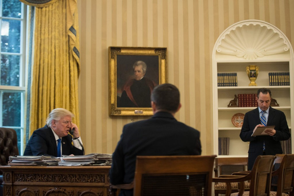 WASHINGTON, DC - JANUARY 28: President Donald Trump speaks on the phone with Chancellor of Germany Angela Merkel in the Oval Office of the White House, January 28, 2017 in Washington, DC. Also pictured at right is White House Chief of Staff Reince Priebus. On Saturday, President Trump is making several phone calls with world leaders from Japan, Germany, Russia, France and Australia. (Photo by Drew Angerer/Getty Images)