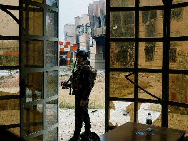 TOPSHOT - A member of the Iraqi special forces' Counter-Terrorism Service (CTS) stands guard next to a damaged building at Mosul's university on January 15, 2017, during an ongoing military operation against Islamic State (IS) group jihadists. Iraqi forces on January 14 retook Mosul's university from the Islamic State jihadist …