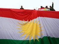TOPSHOT - Iraqi Kurdish youths wave a national flag as they stand above a giant flag of Kurdistan during celebrations of Flag Day on December 17, 2015 in Arbil, the capital of the autonomous Kurdish region in northern Iraq. / AFP / SAFIN HAMED (Photo credit should read SAFIN HAMED/AFP/Getty …