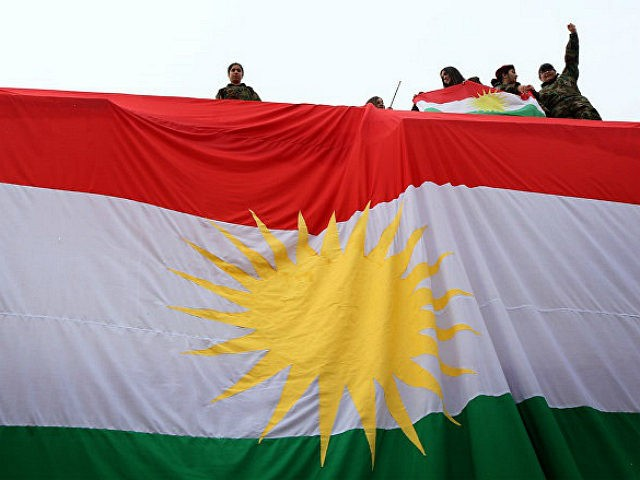 TOPSHOT - Iraqi Kurdish youths wave a national flag as they stand above a giant flag of Kurdistan during celebrations of Flag Day on December 17, 2015 in Arbil, the capital of the autonomous Kurdish region in northern Iraq. / AFP / SAFIN HAMED (Photo credit should read SAFIN HAMED/AFP/Getty Images)