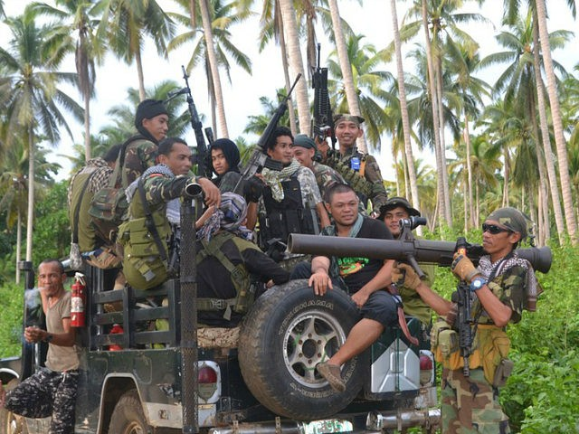 This photo taken on July 29, 2016 shows Muslim rebels from the Moro National Liberation Front (MNLF) aboard a vehicle gathering at a village as they await orders from their leader Nur Misuari in an effort to help rescue remaining hostages of the extremist Abu Sayyaf group in Kalingalang Caluang town, Sulu province in the southern region of Mindanao. Philippine President Rodrigo Duterte has said he wants to meet Misuari to forge peace with Muslim rebels. / AFP / STR (Photo credit should read STR/AFP/Getty Images)