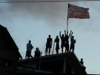 Prisioners atop the roof of the compound celebrate the transfer of their leaders after a negotiation with the police at the Alcacuz Penitentiary, near Natal, Rio Grande do Norte, on January 16, 2017. Authorities thought inmates at the Alcacuz jail near the northeastern city of Natal were under control following the quelling of a deadly riot that broke out Saturday, until some climbed to the roof on Monday. On Sunday, police had stormed the prison and ended a night-long riot. They found 26 prisoners dead, most of them beheaded, officials said. / AFP / ANDRESSA ANHOLETE (Photo credit should read ANDRESSA ANHOLETE/AFP/Getty Images)