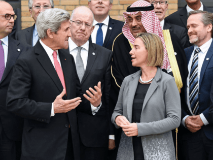 Secretary of State John Kerry (L) speaks with European Union Foreign Policy Chief Federica Mogherini (R) as they take part with other foreign ministers and representatives in a family picture during the Mideast peace conference in Paris on January 15, 2017. Foreign ministers and representatives from around 70 countries are …