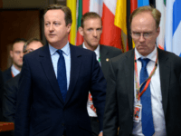 British Prime Minister David Cameron (C) and Britain's ambassador to the European Union, Ivan Rogers (R), leaves after the first day of an EU - Summit at the EU headquarters in Brussels on June 28, 2016.
