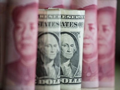 This photo illustration taken on January 6, 2017 shows Chinese 100 yuan notes and one US dollar notes in Beijing. China just raised the exchange rate for the yuan against the US dollar by 0.92 percent from the previous day, the biggest one-day increase in more than 11 years. / …