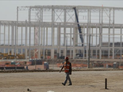 A man walks past a nearly deserted construction site Wednesday in Villa de Reyes, San Luis Potosi, Mexico, as workers shut down operations and remove equipment from the site of a canceled $1.6 billion Ford plant. Ford's cancellation, which costs the region thousands of projected jobs, has sounded alarms in …