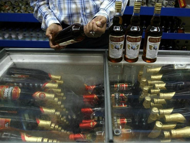 A man checks an alcohol bottle inside a wine shop in Siliguri August 19, 2008. REUTERS/Rupak De Chowdhuri/Files