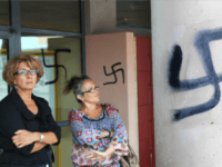 Teachers stand next next to a swastika painted onto a wall of the high school in Agde, in southern France, on September 4, 2008. Some forty swastikas as well as other racist affronts were painted on the night of September 3-4 by one or many unknown persons on the walls …