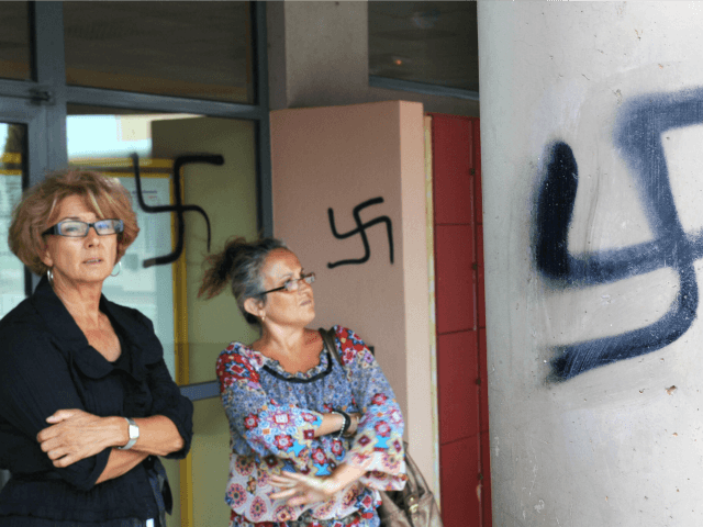 Teachers stand next next to a swastika painted onto a wall of the high school in Agde, in southern France, on September 4, 2008. Some forty swastikas as well as other racist affronts were painted on the night of September 3-4 by one or many unknown persons on the walls of the school. French Education Minister Xavier Darcos 'condemned with upmost firmness these acts of vandalism of a racist character, antisemitism and xenophobia'. AFP PHOTO/BORIS HORVAT (Photo credit should read BORIS HORVAT/AFP/Getty Images)