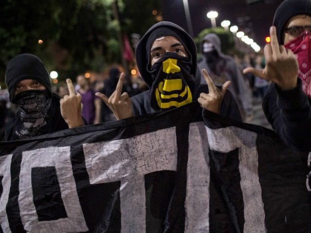 Members of the anarchist group Black Bloc protest against the FIFA World Cup in Rio de Janeiro, Brazil, on May 30, 2014. Brazil has been hit by a wave of strikes and protests against the more than $11 billion being spent on the tournament in a country that desperately needs investment in health, education and transport. AFP PHOTO / YASUYOSHI CHIBA (Photo credit should read YASUYOSHI CHIBA/AFP/Getty Images)