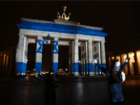 A woman strikes a pose infront of the Brandenburg Gate with the Israeli flag projected onto in Berlin, on January 9, 2017 to pay tribute to the victims of the ramming attack in Jerusalem. Israel was to bury four soldiers on January 9, 2017 killed when a Palestinian rammed a …