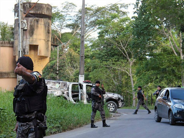 Military police officers track for fugitives of the Anisio Jobim Penitentiary Complex after a riot in the prison left at least 60 people killed and several injured, in Manaus, Amazonia state, Brazil on January 2, 2017. At least 60 people were killed in a prison riot in Brazil's Amazon region …