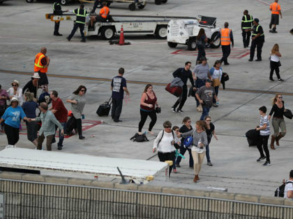 FORT LAUDERDALE, FL - JANUARY 06: People seek cover on the tarmac of Fort Lauderdale-Hollywood International airport after a shooting took place near the baggage claim on January 6, 2017 in Fort Lauderdale, Florida. Officials are reporting that five people were killed and eight wounded in an attack by a …