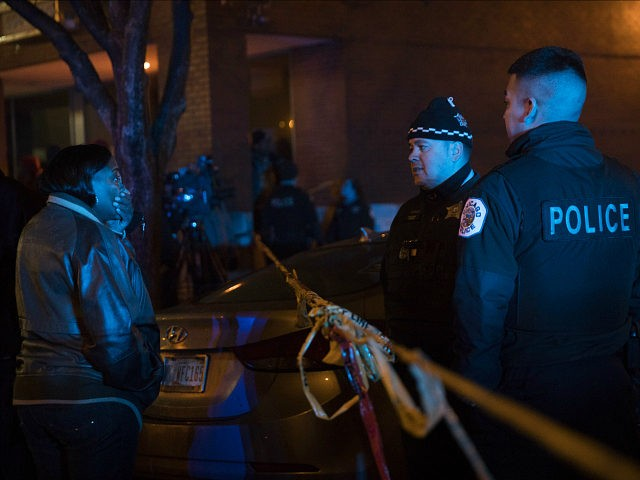 A woman talks with members of the Chicago Police Department at the scene where at least six people were shot, one fatally, on the 8600 block of South Maryland Avenue Sunday, Dec. 25, 2016 in Chicago. (Armando L. Sanchez/Chicago Tribune/TNS via Getty Images)