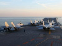 This picture taken on an undisclosed date in December 2016 shows Chinese J-15 fighter jets waiting on the deck of the Liaoning aircraft carrier during military drills in the Bohai Sea, off China's northeast coast. China's Liaoning aircraft carrier battle group has conducted its first exercises with live ammunition, the …