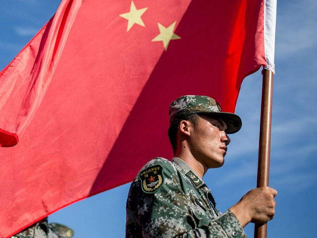 OMSK, RUSSIA - AUGUST 5, 2016: China's serviceman carries a Chinese flag during the opening ceremony for the Maintenance Battalion competition among maintenance units in the village of Cheryomushki as part of the 2016 Army Games, an international event organized by the Russian Defense Ministry. Sergei Bobylev/TASS (Photo by Sergei …