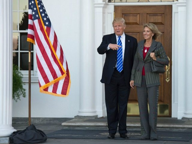 US President-elect Donald Trump poses for a photo with businesswoman Betsy DeVos on the steps of the clubhouse at Trump National Golf Club November 19, 2016 in Bedminster, NJ. / AFP / Don EMMERT (Photo credit should read DON EMMERT/AFP/Getty Images)