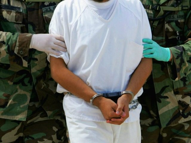 This file photo taken on August 26, 2004 shows a detainee being escorted by military police at Camp 4 of the maximum security prison Camp Delta at Guantanamo (Gitmo) US Naval Base in Guantanamo, Cuba. Six Chinese Muslim Uighurs held at Guantanamo Bay arrived in the Pacific island nation of …