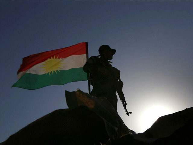 TOPSHOT - An Iraqi Kurdish Peshmerga fighter, next to an Iraqi Kurds flag, holds a position in Sheikh Ali village near the town of Bashiqa, some 25 kilometres north east of Mosul, on November 6, 2016 during an operation against Islamic State (IS) group jihadists to retake the main hub …