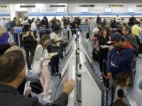 Passengers prepare to check in at Miami International Airport, Wednesday, Nov. 23, 2016, in Miami. Almost 49 million people are expected to travel 50 miles or more for the holiday, the most since 2007, according to AAA. (AP Photo/Alan Diaz)