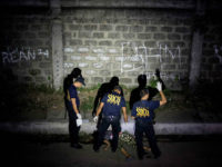 This picture taken on January 5, 2017, shows policemen investigating a crime scene where a woman was shot dead by unidentified gunmen in Manila. People going to mass at one of the most famous churches in the Philippine capital over Christmas were met by a disturbing sight: poster-size pictures of …