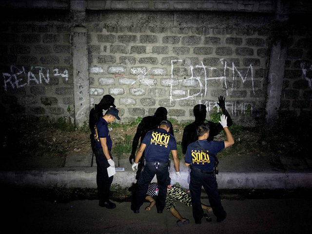 This picture taken on January 5, 2017, shows policemen investigating a crime scene where a woman was shot dead by unidentified gunmen in Manila. People going to mass at one of the most famous churches in the Philippine capital over Christmas were met by a disturbing sight: poster-size pictures of Filipinos dying in pools of blood. The shock Baclaran church exhibit was part of a campaign by one of the nation's oldest and most powerful institutions to stop the killings under President Rodrigo Duterte's war against drugs, which has claimed about 6,000 thousand lives. / AFP / NOEL CELIS / TO GO WITH AFP STORY PHILIPPINES-CRIME-RIGHTS-CATHOLIC-CHURCH,FOCUS BY CECIL MORELLA (Photo credit should read NOEL CELIS/AFP/Getty Images)