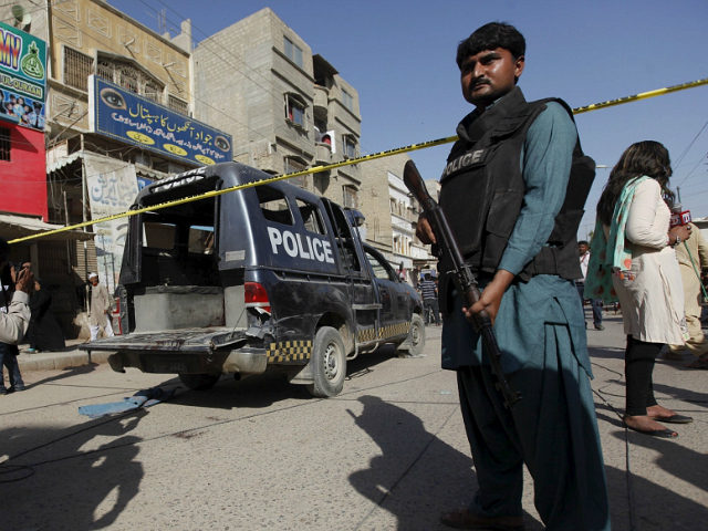 A policeman guards a police vehicle after it was attacked by Taliban gunmen while policemen were guarding medical workers administering polio vaccinations in Karachi, Pakistan April 20, 2016. REUTERS/Akhtar Soomro
