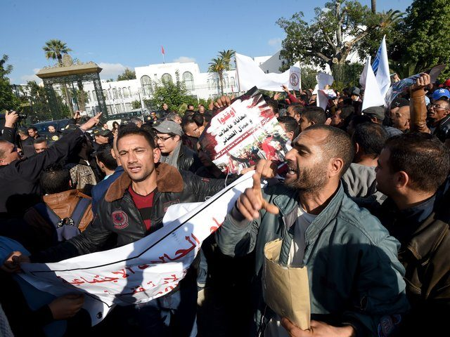 Tunisian unemployed people shout slogans during a demonstration against the government's policy on December 10, 2016 outside the Assembly of the Representatives of the People in Tunis, as the draft budget for 2017 is being reviewed by parliament. / AFP / FETHI BELAID (Photo credit should read FETHI BELAID/AFP/Getty Images)