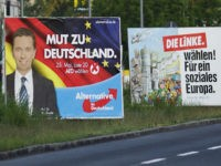 """BERLIN, GERMANY - MAY 20: A cyclist woman carries a pack of toilet paper passing election campaign billboards for the Euro-sceptic Alternative fuer Deutschland (AfD), showing party head Bernd Lucke, and a billboard of the Die Linke party showing the slogan """"Die Linke waehlen ! Fuer ein soziales Europa"""" (The …"""