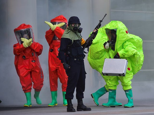 South Korean rescue members wearing chemical protective suits gesture as an armed policeman (C) stands guard during an anti-terror drill as part of a disaster management exercise at the COEX shopping and exhibition center in Seoul on May 20, 2016. South Korea is holding its 2016 Safe Korea anti-disaster exercise …
