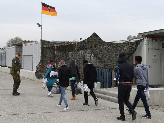 Migrants walk to get the first registration at the registration point for asylum seekers in Erding near Munich, southern Germany, on November 15, 2016. The refugees from Eritrea came by plane from Italy. / AFP / CHRISTOF STACHE (Photo credit should read CHRISTOF STACHE/AFP/Getty Images)