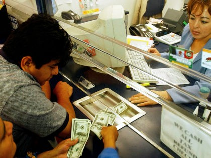 Alfonsa Morales, left, counts money she and her son Hector Gonzalez are handing to Eteldina Romero to be sent to Mexico, at Popular Cash Express #2 in Los Angeles, Monday, Dec. 30, 2002. Morales and Gonzalez sent $650 to a friend in a small village in Oaxaca as a New …