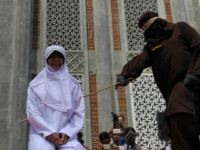 A religious officer canes an Acehnese youth onstage as punishment for dating outside of marriage, which is against sharia law, outside a mosque in Banda Aceh on August 1, 2016. The strictly Muslim province, Aceh has become increasingly conservative in recent years and is the only one in Indonesia implementing …