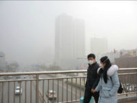 Pedestrians wearing face masks walk on a footbridge in heavy smog in Handan city, north China's Hebei province, 2 January 2017. Heavy smog in northern China caused hundreds of flights to be canceled and highways to shut on Sunday (1 January 2017), disrupting the first day of the New Year …