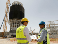 Eran Gartner (L), the Chief Executive Officer of Megalim Power Ltd, speaks with a Spanish worker in charge of the welders in front of the solar receiver at the construction site of the Ashalim solar tower near the southern Israeli kibbutz of Ashalim in the Negev desert on May 26, 2016.