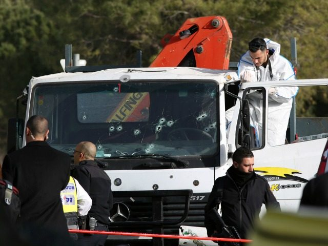 An Israeli forensics expert gathers evidence as security forces and emergency personnel gather at the site of a vehicle-ramming attack in Jerusalem on January 8, 2017. Four Israeli soldiers were killed when they were run down by a truck in Jerusalem in what police were treating as a deliberate attack, …