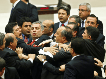 Ruling Justice and Development Party lawmakers (R) and main opposition Republican People's Party scuffle during a debate focused on corruption charges against four cabinet ministers of Turkish Prime Minister, at the parliament in Ankara, on May 5, 2014. AFP PHOTO / ADEM ALTAN (Photo credit should read ADEM ALTAN/AFP/Getty Images)