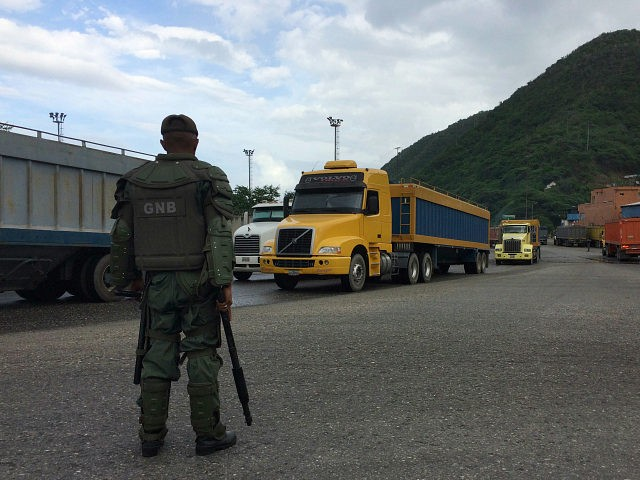 In this Dec. 19, 2016 photo, a National Guard soldier watches over cargo trucks leaving the port in Puerto Cabello in Venezuela, the port city that handles the majority of the country's food imports. Across the chain of command, from high-level generals to the lowest foot soldiers, military officials are using their growing power over the food supply to siphon off wealth for themselves. (AP Photo/Ricardo Nunes)