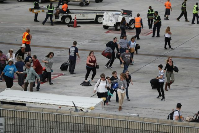 People seek cover on the tarmac of Fort Lauderdale-Hollywood International airport after a shooting took place near the baggage claim on January 6, 2017 in Fort Lauderdale, Florida