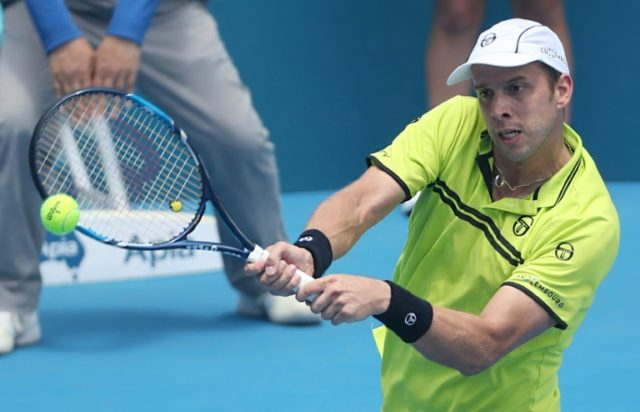Gilles Muller of Luxembourg hits a return to Pablo Cuevas of Uruguay in their men's quarter-final match at the Sydney International tennis tournament, on January 12, 2017