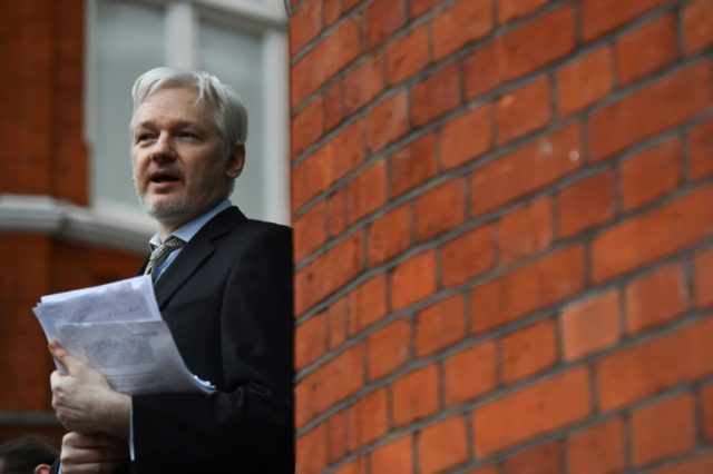 WikiLeaks founder Julian Assange addressing the media and holding a printed report of the judgement of the UN's Working Group on Arbitrary Detention on his case from the balcony of the Ecuadorian Embassy in central London on February 5, 2016