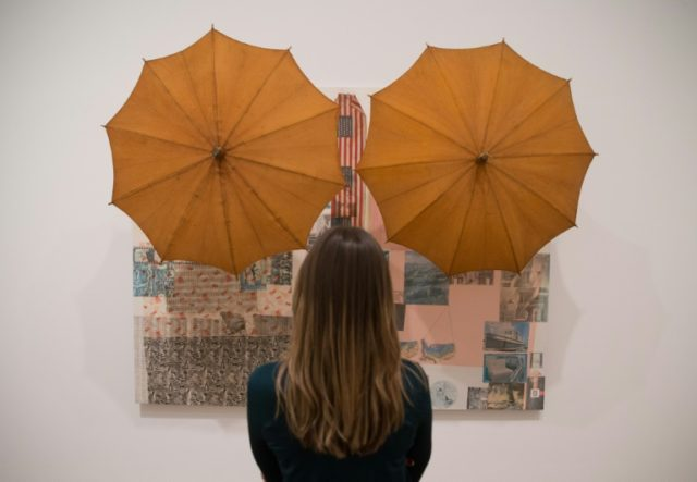A woman looks at an art work entitled 'Untitled (Spread), 1983' by US artist Robert Rauschenberg during a press preview at the Tate Modern in London on November 29, 2016