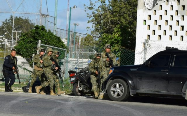 Police and soldiers take cover during an attack on the Quintana Roo state prosecutor's office in Cancun, Mexico, which left the gunman and two staff dead
