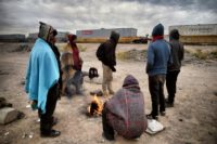 Migrants warm themselves next to a campfire near train tracks in Sonora state, Mexico close to the border with the United States