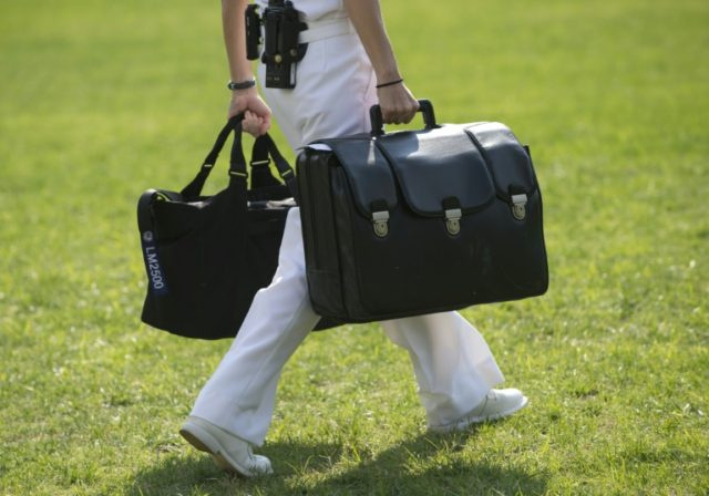 "A White House military aide and member of the US Navy carries a briefcase known as the ""football,"" containing emergency nuclear weapon codes"